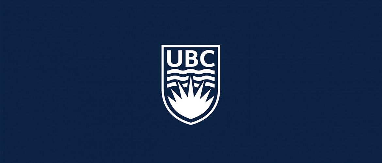 White UBC crest on a dark blue background